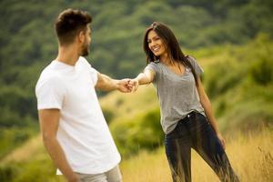 lyckligt ungt par i kärlek som går genom gräset foto