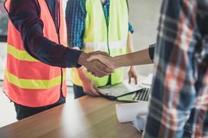 två byggnadsarbetare som skakar hand foto