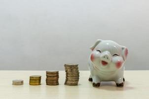 vit spargris och mynt pengar på ett träbord. begreppet ekonomi och spara pengar, investeringar eller pensionsålder i framtiden foto