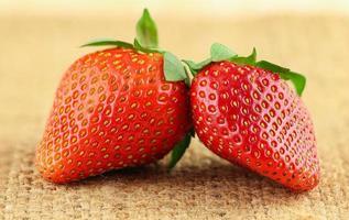 närbild av två jordgubbar på säckvävmatta foto