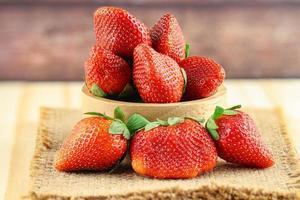 jordgubbar i träskål och säckvävsmatta foto