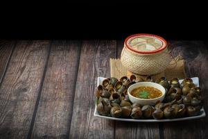 kokt snigel med thailändsk kryddig chilisås på vit platta och klibbig riskorg på ett träbord