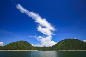 moln över gröna kullar och vatten