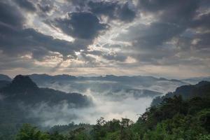 soluppgång genom moln på dimmiga berg foto
