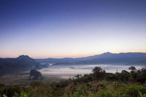 soluppgång ovanför dimmiga berg