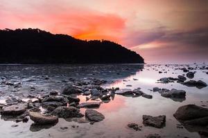 färgrik solnedgång över en stenig strand