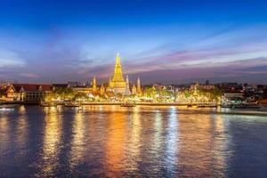 tempel- och stadsljus reflekterade i vatten foto