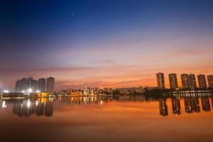 bygga reflektion i vatten vid solnedgången foto