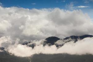 moln och dimma som omger bergen foto