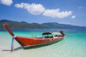 röd lång båt på en strand