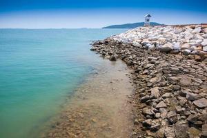 stenig strand och klart blått vatten foto