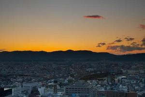 soluppgång över en stad med berg