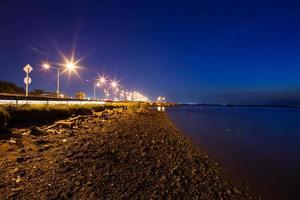 väg nära vatten på natten foto