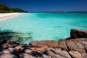 klart vatten och stenar på en strand foto