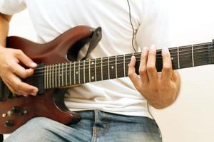 man spelar elgitarr