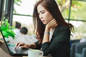 asiatisk affärskvinna som arbetar på ett kafé foto