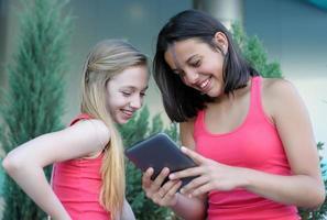 två tjejer som har kul med en surfplatta foto