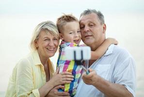 farföräldrar och barnbarn tar en selfie