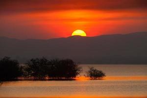solnedgång bakom ett berg foto