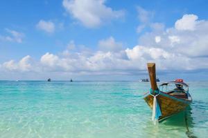 lång båt som flyter på en tropisk strand foto