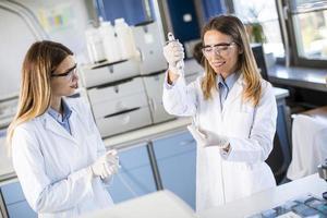 kvinnliga forskare i den vita laboratoriekusten som arbetar i laboratoriet foto