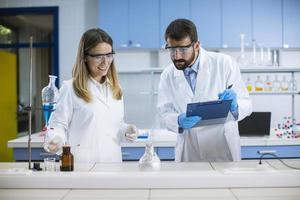forskare gör experiment med rök på ett bord i ett kemilaboratorium foto