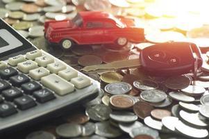bilnyckel och röd modellbil med mynt