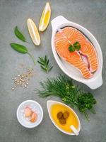 laxfilé i en vit skål med ingredienser foto