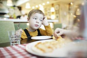 uttråkad liten pojke på en restaurang