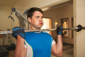 stark ung man tränar med skivstång
