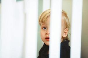 barn i en vit spjälsäng