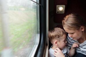 mamma och son på en tågresa foto
