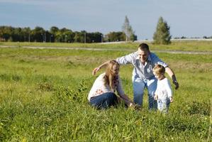 far som leker med sin fru och son foto