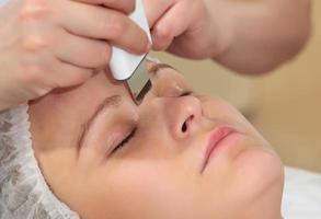 kvinna får en ultraljud ansiktsrengöring foto