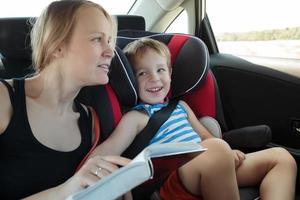 mamma som läser en bok till sonen i bilen foto