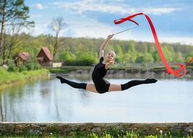 ung gymnast som hoppar med ett band foto