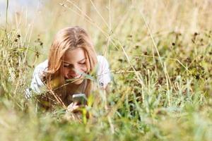 flicka med en telefon som lägger i gräset