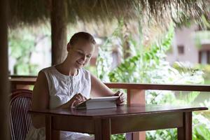 kvinna som använder minnestavlan i ett utomhuscafé foto