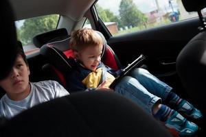 två pojkar på baksätet i en bil foto