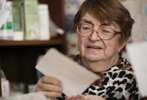 äldre kvinna som läser ett brev foto