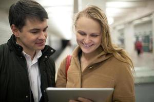 ungt par som använder en tablett i en tunnelbanestation