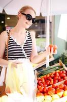 ung kvinna som shoppar efter färska tomater foto