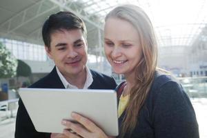 ung man och kvinna i ett köpcentrum med en tablett foto