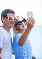 glada par i solglasögon tar en selfie foto