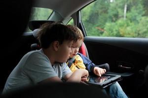 pojkar som använder en surfplatta i en bil foto