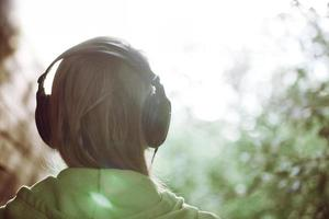 kvinna i hörlurar mot starkt solljus