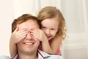 dotter som spelar peekaboo med far foto