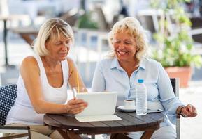 två mogna kvinnor som använder en tablett foto
