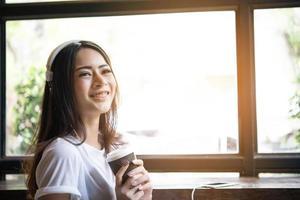 ung kvinna lyssnar på musik i hörlurar med fönsterbrädan bakgrund. foto
