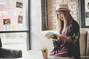 glad affärskvinnaläsebok medan du kopplar av på kaféet